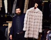有胡子和髭的人拿着外套 冬天衣物概念 免版税图库摄影