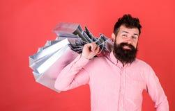 有胡子和髭的人运载在肩膀,红色背景的购物袋 凉快的面孔的行家是购物使上瘾 免版税库存图片
