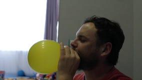 有胡子和髭的滑稽的人膨胀有他的嘴的一个黄色气球 股票录像
