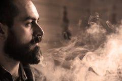 有胡子和Mustages的Vaping人一根电子香烟 Vaper行家烟蒸发器和Exhals烟圆环 库存照片