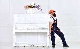 有胡子工作者的人盔甲和总体的推挤,努力移动钢琴,白色背景 传讯者交付家具 免版税库存图片