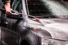 有胡子或汽车洗衣机的一个人在商店洗涤的晚上洗涤有一台高压洗衣机的一辆灰色汽车 库存图片