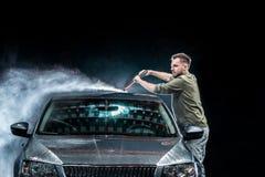 有胡子或汽车洗衣机的一个人在晚上洗涤有一台高压洗衣机的一辆灰色汽车在街道 库存照片