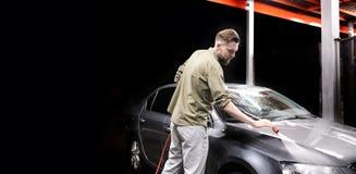 有胡子或汽车洗衣机的一个人在洗车的晚上洗涤有高压用具的一辆灰色汽车 图库摄影