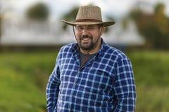 有胡子残酷强壮男子在牛仔帽ulybayutsya和愉快的生活中,有很多阳和乐观 免版税图库摄影