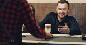 有胡子的一个人和一个可爱的浅黑肤色的男人在酒吧坐并且观看电话 股票视频