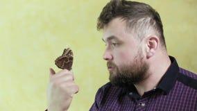 有胡子的一个人拿着一只蝴蝶4k 股票视频