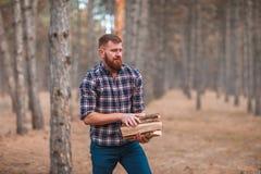 有胡子的一个人拿着木柴 在森林里 免版税库存图片