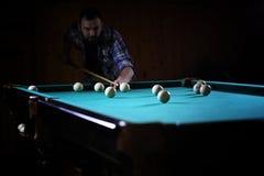 有胡子的一个人播放大台球 在12英尺水池的党 库存照片