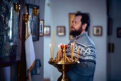 有胡子的一个俄国人在东正教,光里站立每蜡烛并且在象前面祈祷 免版税库存照片