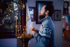 有胡子的一个俄国人在东正教,光里站立每蜡烛并且在象前面祈祷 库存照片