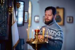 有胡子的一个俄国人在东正教,光里站立每蜡烛并且在象前面祈祷 图库摄影