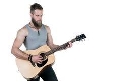 有胡子的一个吸引人人拿着一把声学吉他,在白色被隔绝的背景 水平的框架 免版税库存照片