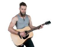 有胡子的一个吸引人人拿着一把声学吉他,在白色被隔绝的背景 水平的框架 免版税库存图片