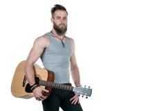 有胡子的一个吸引人人拿着一把声学吉他,在白色被隔绝的背景 水平的框架 库存照片