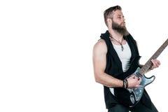 有胡子的一个吸引人人拿着一把电吉他,在白色被隔绝的背景 水平的框架 免版税图库摄影