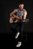 有胡子的一个吸引人人,弹一把声学吉他,在黑色被隔绝的背景 垂直的框架 库存照片
