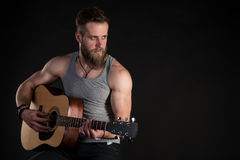 有胡子的一个吸引人人,弹一把声学吉他,在黑色被隔绝的背景 水平的框架 库存图片
