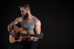 有胡子的一个吸引人人,弹一把声学吉他,在黑色被隔绝的背景 水平的框架 免版税库存照片