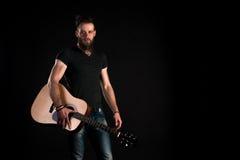 有胡子的一个吸引人和时髦的人站立与在黑色被隔绝的背景的一把声学吉他 水平的框架 免版税库存图片