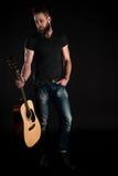 有胡子的一个吸引人和时髦的人站立全长与在黑背景的一把声学吉他 垂直的fra 免版税库存图片