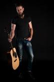 有胡子的一个吸引人和时髦的人站立全长与在黑色被隔绝的背景的一把声学吉他 垂直的fra 库存图片