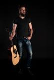 有胡子的一个吸引人和时髦的人站立全长与在黑色被隔绝的背景的一把声学吉他 垂直的fra 免版税库存图片