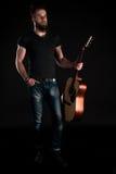 有胡子的一个吸引人和时髦的人站立全长与在黑色被隔绝的背景的一把声学吉他 垂直的fra 免版税图库摄影