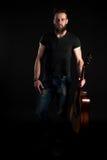 有胡子的一个吸引人和时髦的人站立全长与在黑色被隔绝的背景的一把声学吉他 垂直的fra 库存照片