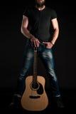 有胡子的一个吸引人和时髦的人站立全长与在黑色被隔绝的背景的一把声学吉他 垂直的fra 图库摄影