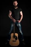 有胡子的一个吸引人和时髦的人站立全长与在黑色被隔绝的背景的一把声学吉他 垂直的fra 免版税库存照片