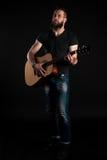有胡子的一个吸引人和时髦的人站立全长并且弹一把声学吉他,在黑背景 Vertic 库存图片
