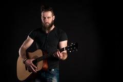 有胡子的一个吸引人和时髦的人站立并且弹在黑色被隔绝的背景的一把声学吉他 水平的框架 库存图片