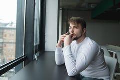 有胡子的一个年轻人在一个现代办公室在电话坐在桌上在窗口附近并且谈话 库存照片