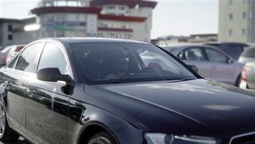 有胡子的一个年轻人在停车场乘坐在他的黑汽车 企业轿车沿其他机器平静地移动 股票录像