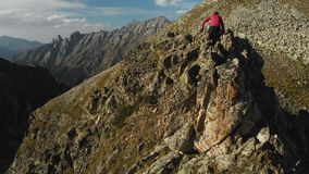 有胡子的一个年轻人,盖帽的一名登山家和太阳镜,攀登在山的岩石土坎上流 Parkour 影视素材