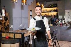 有胡子的一个英俊的年轻人在站立在餐馆和拿着有飞蛾的围裙穿戴了一块白色板材 反对 免版税库存照片