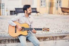 有胡子的一个逗人喜爱的时髦的人坐在街道的具体遏制并且弹一把声学吉他并且微笑 音乐家享用 免版税图库摄影