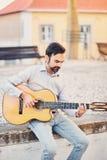 有胡子的一个逗人喜爱的时髦的人坐在街道的具体遏制并且弹一把声学吉他并且微笑 音乐家享用 库存照片