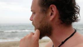 有胡子的一年轻人和在情感游泳的蓝眼睛在对照相机和微笑的海谈话以后 4个k videoa年轻人 股票视频
