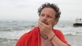有胡子的一年轻人和在海的背景的蓝眼睛在沐浴接触和冲程以后他的胡子 4?k?? 股票视频