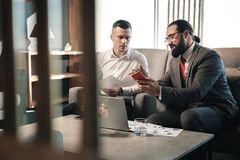 有胡子的上司和他的年轻实习生坐沙发,当谈话时 图库摄影
