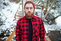 有胡子的严肃的人在冬天森林的格子花呢上衣 图库摄影