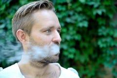 年轻有胡子的人侧视图抽烟 库存图片