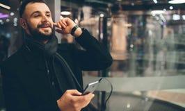 年轻有胡子的人侧视图,穿戴的incasual穿戴,他在街道上站立并且使用智能手机和听 免版税库存照片