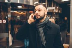 年轻有胡子的人侧视图,穿戴的incasual穿戴,他在街道上站立并且使用智能手机 免版税库存照片
