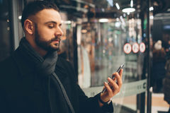 年轻有胡子的人侧视图,穿戴的incasual穿戴,他在街道上站立并且使用智能手机 库存图片