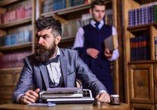 有胡子的人和严密的面孔与打字机一起使用 免版税库存照片