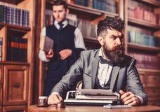 有胡子的人和严密的面孔与打字机一起使用 库存照片