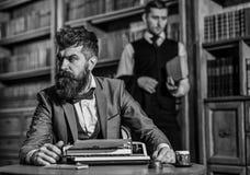 有胡子的人和严密的面孔与打字机一起使用 免版税库存图片